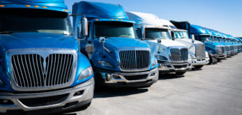 Large fleet of commercial trucks 18 wheelers parked in truck yard